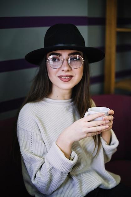 Положительная элегантная молодая женщина в шляпе и очках с кружкой напитка Бесплатные Фотографии