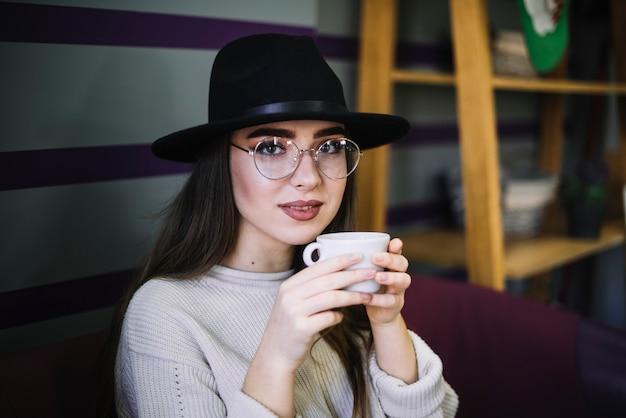 Элегантная молодая женщина в шляпе и очках с кружкой напитка Бесплатные Фотографии