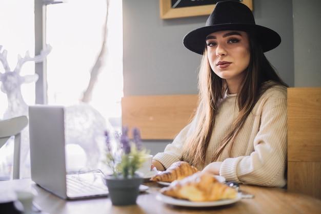 Элегантная молодая женщина в шляпе с ноутбуком и круассанами за столом в кафе Бесплатные Фотографии