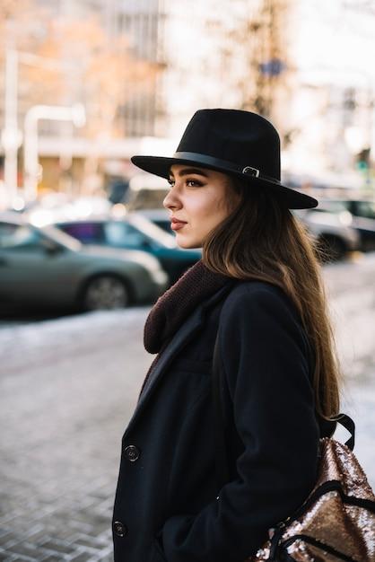 Элегантная молодая женщина в шляпе и пальто на улице Бесплатные Фотографии