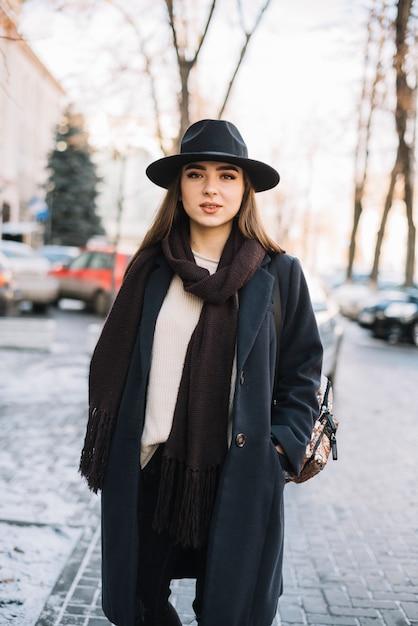帽子と路上でスカーフでコートでエレガントな若い女性 無料写真