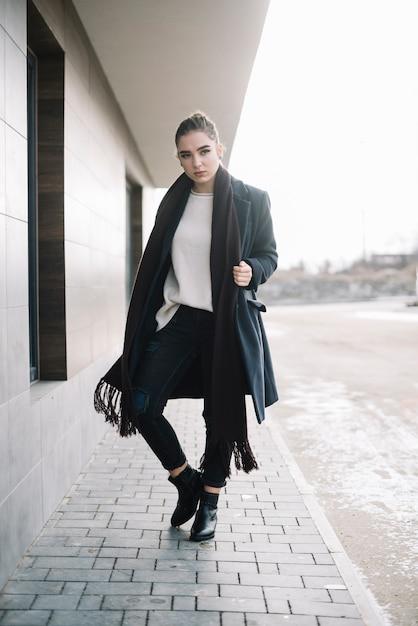 路上でスカーフとコートを着たエレガントな若い女性 無料写真