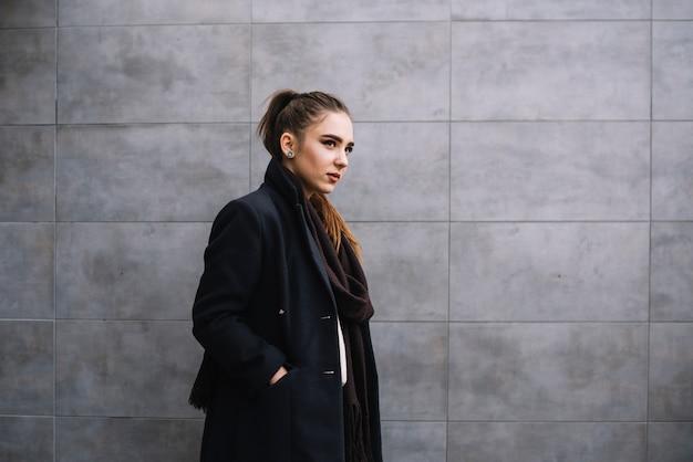 灰色の壁の近くのスカーフとコートを着たスタイリッシュな若い女性 無料写真