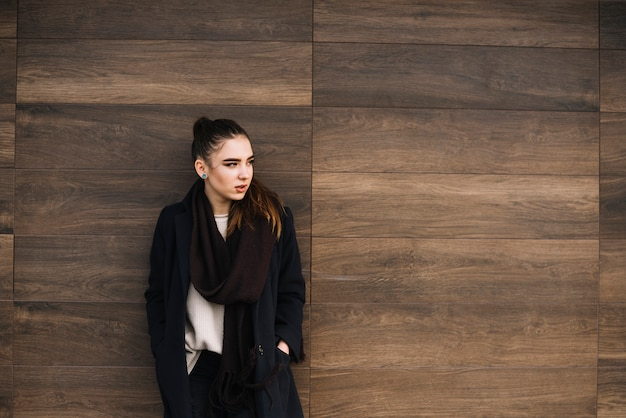 木製の壁の近くのスカーフでコートを着たエレガントな若い女性 無料写真