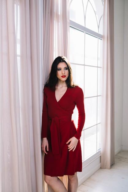 部屋の窓の近くの赤いドレスでエレガントな若い女性 無料写真