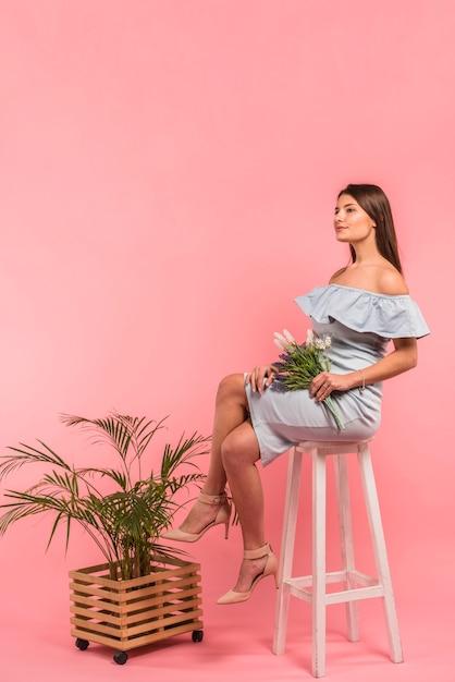 花の花束を椅子に座っている女性 無料写真