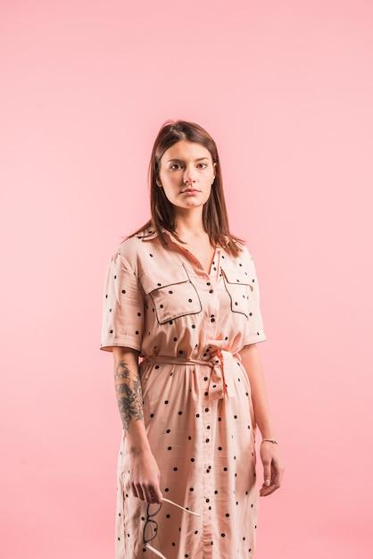 ピンクの背景のドレスの女 無料写真