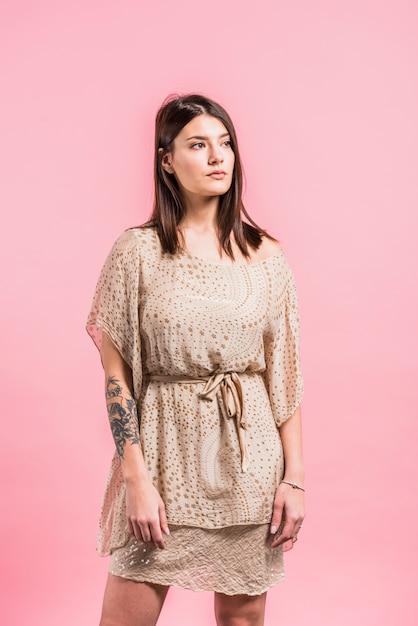 ピンクの背景のドレスで思いやりのある女性 無料写真