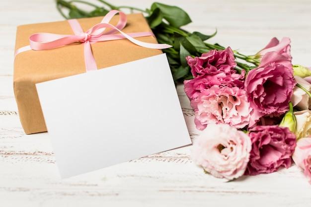 プレゼントボックスと花の近くの紙 無料写真