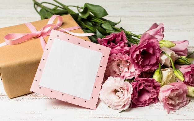 Бумажная рамка возле подарочной коробки и цветов Бесплатные Фотографии