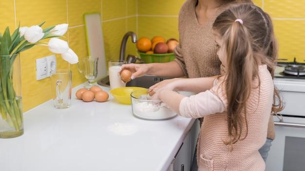 母と娘は台所で料理を 無料写真
