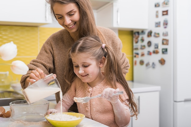 Мать и дочь наливают молоко в миску Бесплатные Фотографии