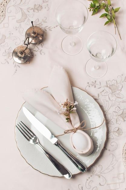 Салфетка и столовые приборы на тарелке возле стаканов и растений Бесплатные Фотографии