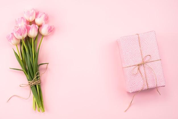 ピンクのテーブルの上のギフトボックスとチューリップの花束 無料写真