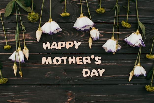 テーブルの上の花との幸せな母の日碑文 無料写真