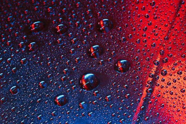 赤と青の織り目加工の背景を持つガラス上の水滴 無料写真