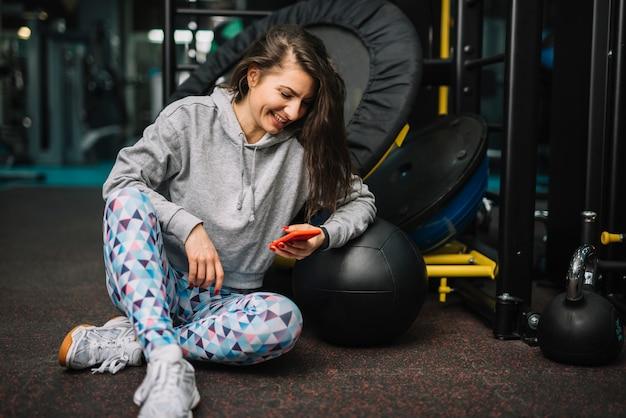 スマートフォンのジムで運動の笑顔の女性 無料写真