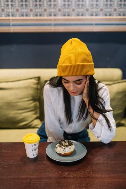 カフェのテーブルで一杯の飲み物の近くの皿にデザートを持つ若い女 無料写真