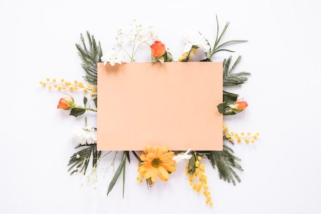 テーブルの上の別の花に空白の紙 無料写真