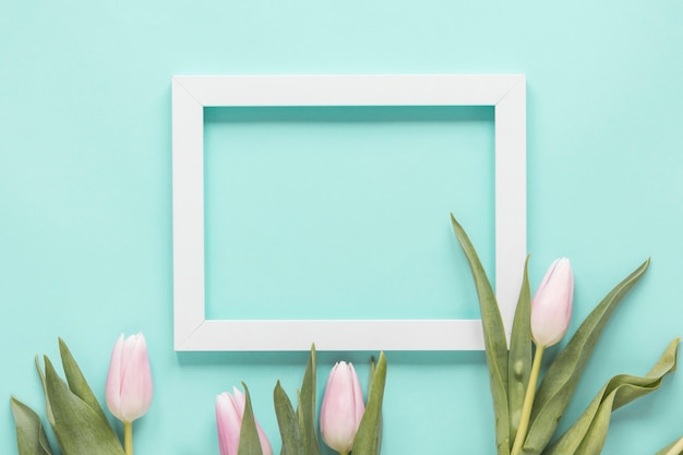 青いテーブルの上の空白のフレームとチューリップの花 無料写真