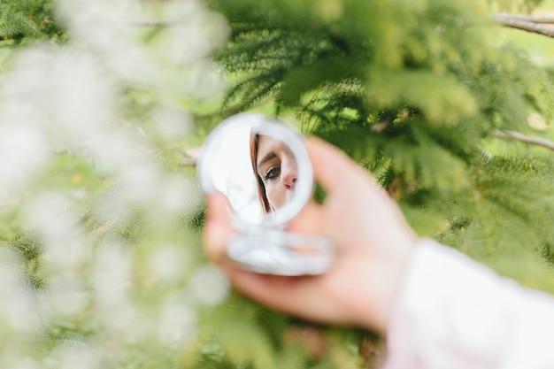 手の鏡の中の女性の反射 無料写真