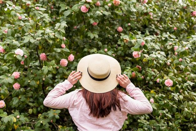Женщина в шляпе возле розовых цветов, растущих на зеленых веточек Бесплатные Фотографии