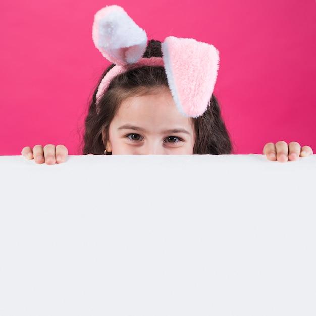 テーブルの後ろに隠れているバニーの耳の中の少女 無料写真