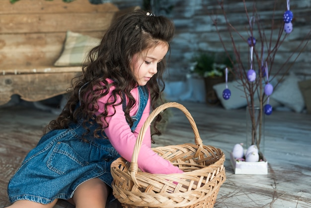 イースターエッグの近くのバスケットに探している小さな女の子 無料写真