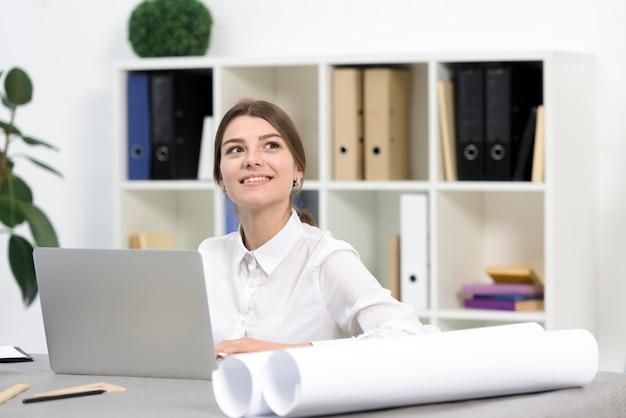 オフィスでラップトップを使用しながら空想幸せな若い実業家 無料写真