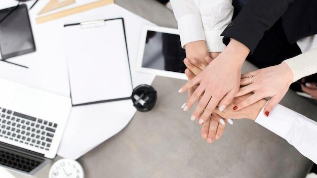 机の上に互いの手を重ねる実業家 無料写真