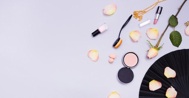 Роза; лепестки; овальная щетка; лак для ногтей; помада и ожерелье на фиолетовом фоне Бесплатные Фотографии
