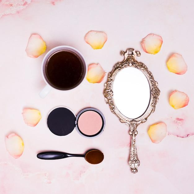 Чашка кофе; лепестки; компактная пудра; овальная кисточка и компактная пудра на розовом фоне Бесплатные Фотографии