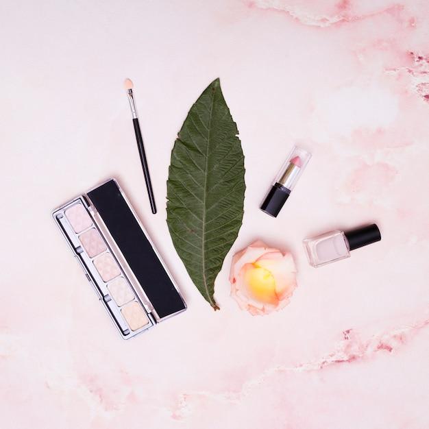 Зеленый лист; помады; лак для ногтей; лепестки; макияж кисти и палитра теней на розовом фоне Бесплатные Фотографии