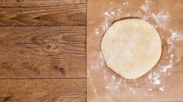 Сырье круглое раскатать тесто на пергаментной бумаге над деревянным столом Бесплатные Фотографии