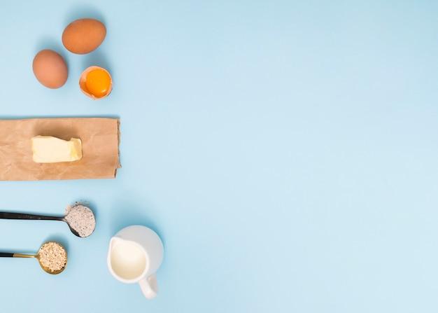 エンバク納屋で計量スプーン。小麦粉;卵;バターとミルク、ブルーの背景 無料写真