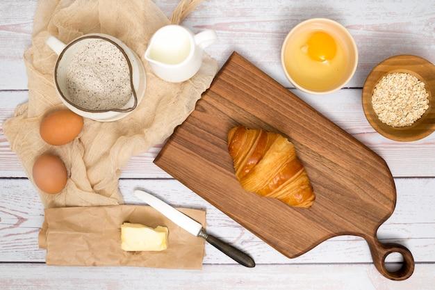 Запеченный круассан на разделочную доску с ингредиентами на деревянной доске Бесплатные Фотографии