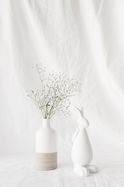 花瓶とウサギの姿の花を持つ植物の小枝 無料写真
