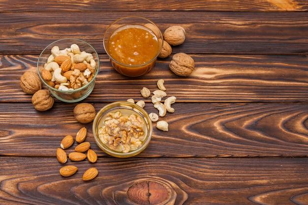 木製のテーブルの上に蜂蜜とさまざまなナッツ 無料写真