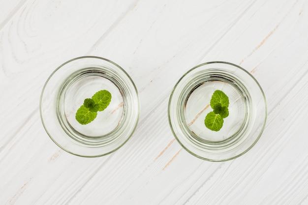 白いテーブルの上のグラスにミントと水します。 無料写真