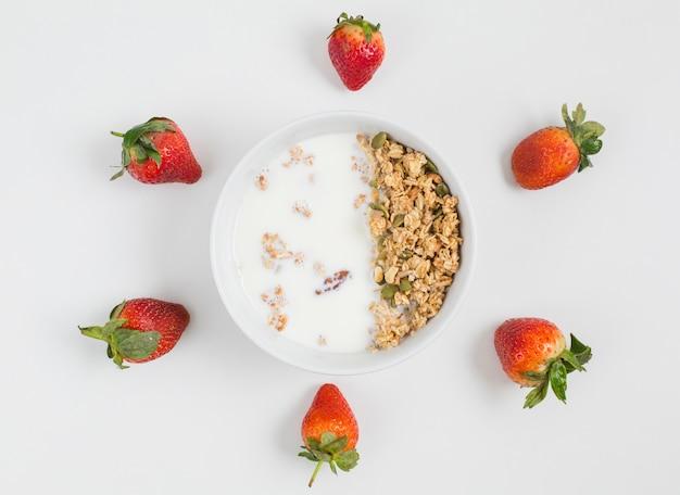 白い背景で隔離の牛乳と自家製オートミールのボウルで飾られた全体のイチゴ 無料写真