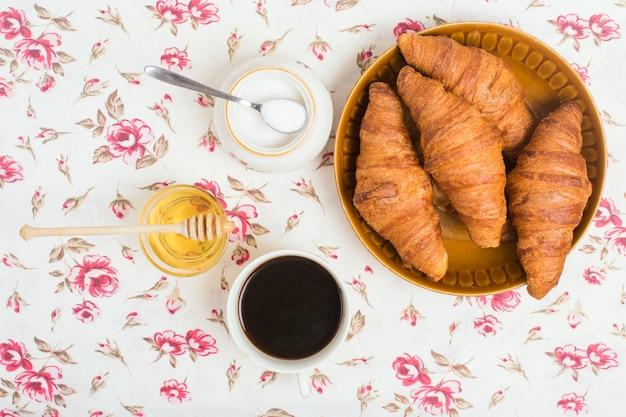 焼きたてのクロワッサン。お茶;花の背景に蜂蜜と粉ミルク 無料写真