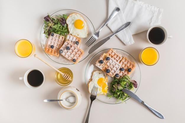 ジュースグラスティーカップはちみつ;粉ミルクとワッフルのプレート。白い背景の上のサラダと目玉焼き 無料写真