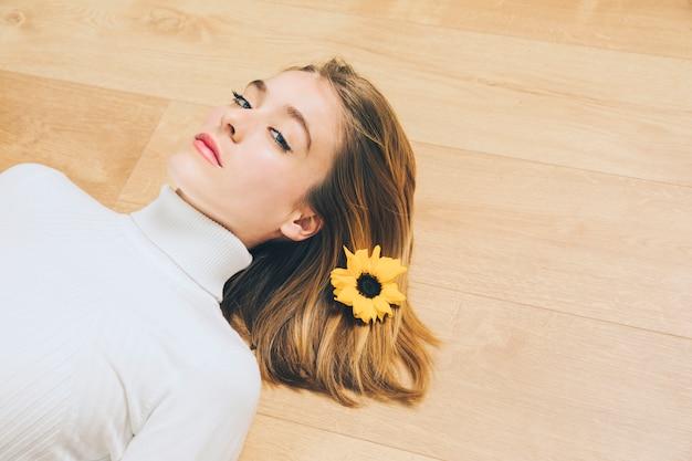 床に横になっている髪の明るい花を持つ思いやりのある女性 無料写真