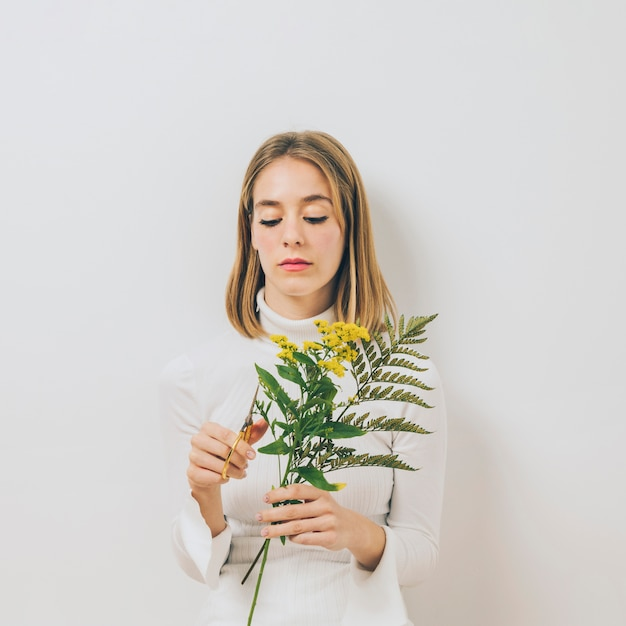 Белокурая молодая женщина срезает цветы ножницами Бесплатные Фотографии