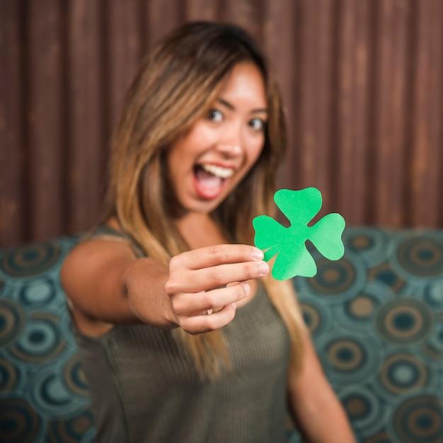 グリーンペーパークローバーを持って泣いている幸せな女 無料写真