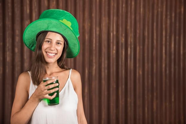 飲み物のガラスを持つ陽気な若い女性 無料写真