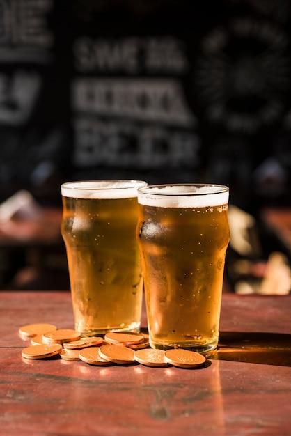 テーブルでコインのヒープ近くの飲み物のグラス 無料写真