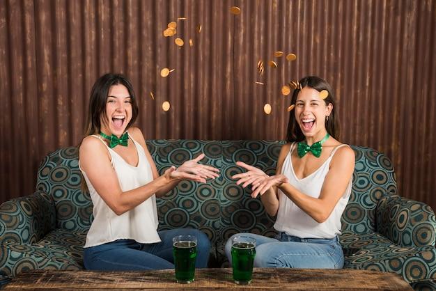 飲み物のグラスとテーブルの近くにコインを投げて幸せな若い女性 無料写真