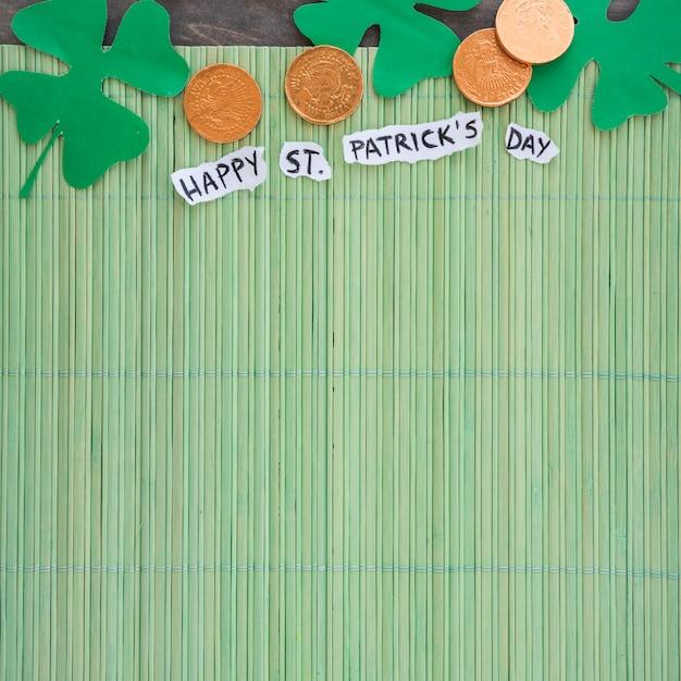 Бумажные клевер рядом с монетами и счастливый день святого патрика на бамбуковой циновке Бесплатные Фотографии