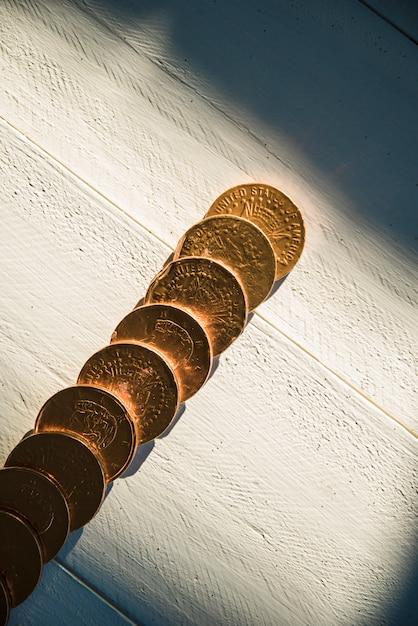 ボード上の黄金のコインと暗闇の中で太陽の光 無料写真